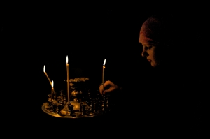 A young woman lights a candle in an Orthodox Church in the Ukraine [Image: Wiki Commons]