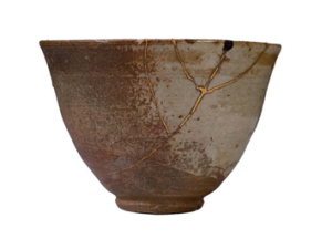 A piece of pottery that broke, was repaired with gold, and is now Kintsukoroi. Do you see the Rune symbol?(Image shared on a Kintsukoroi post on Camiimac.)