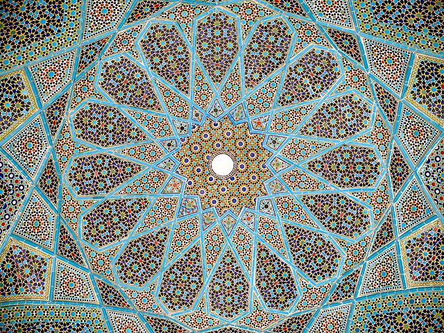 The mosaic-tiled ceiling of the roof of Hafez's tomb in Shiraz, Iran. CC Image by Pentocello, Apri 2008, and shared via Wikimedia.