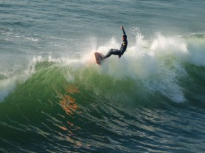 Longboard Surfer On The Wave Crest at Huntington Beach, CA, 31 December 2007, by Andrew Schmidt. Public domain photo via pdpics dot net.