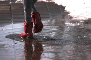 Red boots and puddles. Public domain image from Pixabay.